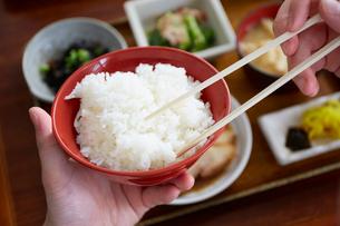 定食のご飯を食べようとしている男性の手元の写真素材 [FYI03137687]