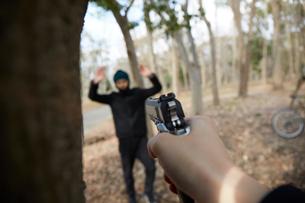 怪しい人に向かって銃を構えている手の写真素材 [FYI03137692]