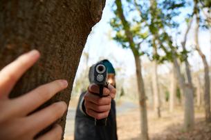 こちらに向かって銃を構えている男性の写真素材 [FYI03137693]