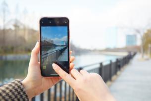 スマートフォンで景色を撮る女性の手元の写真素材 [FYI03137694]