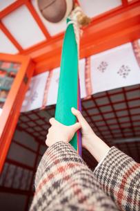 神社の鈴緒に手をかけた女性の手元の写真素材 [FYI03137695]