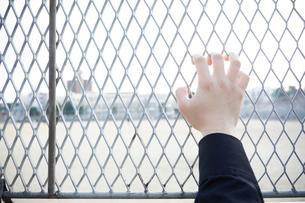 フェンスにかけた男性の右手の写真素材 [FYI03137698]