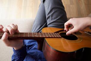 アコースティックギターを弾く男性の手元の写真素材 [FYI03137730]