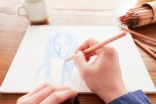 テーブルの上でスケッチブックに女性の絵を描く男性の手元の写真素材 [FYI03137735]