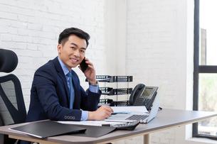 携帯電話を使うビジネスマンの写真素材 [FYI03139932]