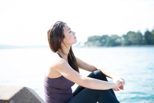 水辺に座って目を瞑っている女性の写真素材 [FYI03140231]