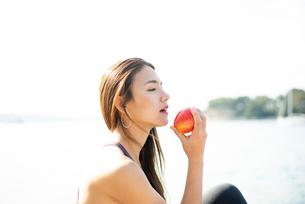 水辺でリンゴを食べている女性の写真素材 [FYI03140313]