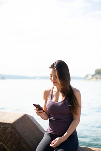 ジム着で水辺でスマホを見ている女性の写真素材 [FYI03140363]