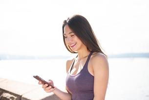 ジム着でスマホを持って笑っている女性の写真素材 [FYI03140371]