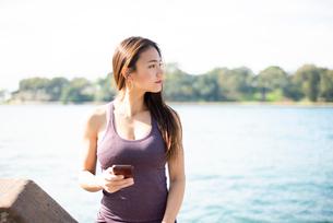 ジム着で水辺でスマホを持っている女性の写真素材 [FYI03140407]