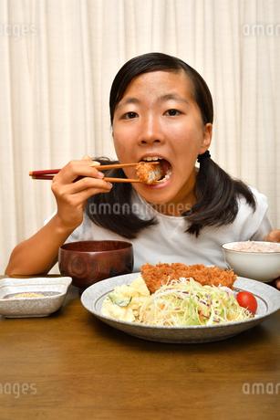 トンカツ定食を食べる女の子の写真素材 [FYI03140483]