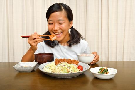 トンカツ定食を食べる女の子の写真素材 [FYI03140486]