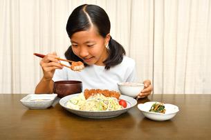 トンカツ定食を食べる女の子の写真素材 [FYI03140487]