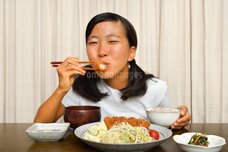 トンカツ定食を食べる女の子の写真素材 [FYI03140488]