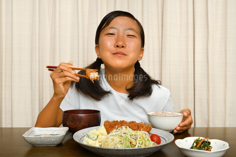 トンカツ定食を食べる女の子の写真素材 [FYI03140489]