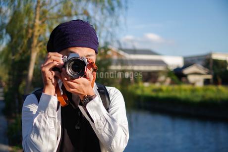 柳川の街並みを記念に残そうとしている男性観光客の写真素材 [FYI03140508]