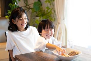 姉の膝の上に座っておやつを食べながら微笑む男の子の写真素材 [FYI03140593]