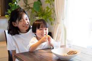 姉の膝の上に座っておやつを食べながら微笑む男の子の写真素材 [FYI03140594]