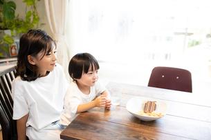 姉の膝の上に座っておやつを食べながら微笑む男の子の写真素材 [FYI03140597]