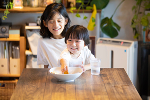姉の膝の上に座っておやつを食べながら微笑む男の子の写真素材 [FYI03140598]