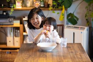 姉の膝の上に座っておやつを食べながら微笑む男の子の写真素材 [FYI03140599]