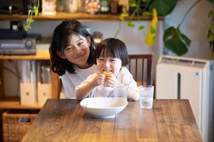 姉の膝の上に座っておやつを食べながら微笑む男の子の写真素材 [FYI03140600]