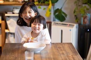 姉の膝の上に座っておやつを食べながら微笑む男の子の写真素材 [FYI03140601]