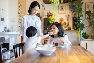 姉に食べ物を食べさせる男の子とそれを見守る母親の写真素材 [FYI03140620]