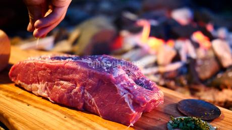 ステーキの下準備に塊の牛肉に調味料を振るの写真素材 [FYI03142297]