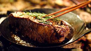 屋外で肉の塊をローストするキャンプ飯の写真素材 [FYI03142300]