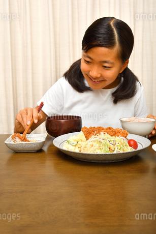 トンカツ定食を食べる女の子の写真素材 [FYI03142411]