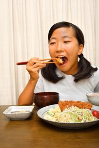 トンカツ定食を食べる女の子の写真素材 [FYI03142413]