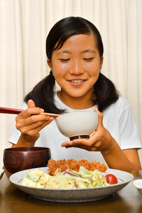 トンカツ定食を食べる女の子の写真素材 [FYI03143252]