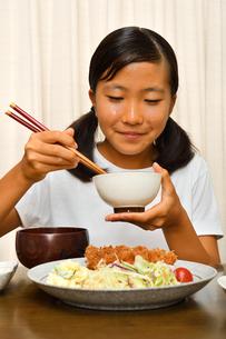 トンカツ定食を食べる女の子の写真素材 [FYI03143632]