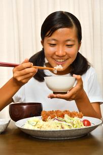 トンカツ定食を食べる女の子の写真素材 [FYI03143633]