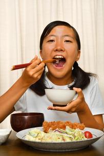 トンカツ定食を食べる女の子の写真素材 [FYI03143634]