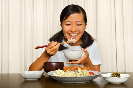 トンカツ定食を食べる女の子の写真素材 [FYI03143642]