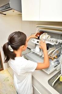 食洗器で食器を洗浄する女の子(後姿)の写真素材 [FYI03144281]