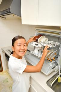 食洗器で食器を洗浄する女の子の写真素材 [FYI03144282]