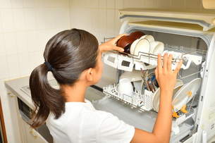 食洗器で食器を洗浄する女の子(後姿)の写真素材 [FYI03144283]