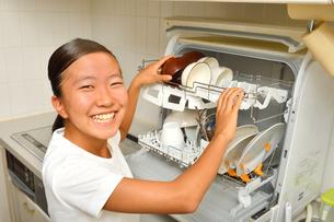 食洗器で食器を洗浄する女の子の写真素材 [FYI03144284]