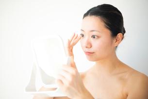 鏡で自分の顔を見ている女性の写真素材 [FYI03144969]