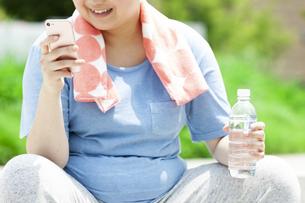 スマートフォンを持つ太った女性の手元の写真素材 [FYI03145552]