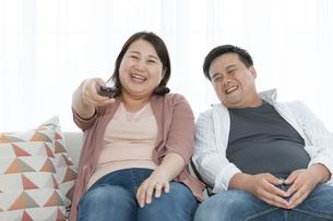 テレビを見る太ったカップルの写真素材 [FYI03145587]