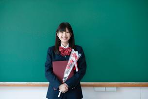 卒業証書と花を持ち微笑む女子学生の写真素材 [FYI03145807]
