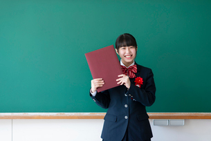 卒業証書を持ち微笑む女子学生の写真素材 [FYI03145814]