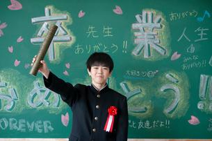 卒業証書を持ち微笑む男子学生の写真素材 [FYI03145829]