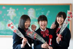 花を持ち微笑む女子学生の写真素材 [FYI03145833]
