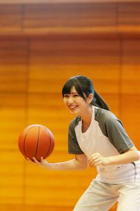 体育館でバスケットをする女子学生の写真素材 [FYI03145910]
