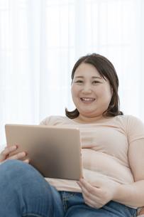 タブレットPCを見る太った女性の写真素材 [FYI03146068]